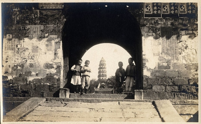 Four Chinese boys standing in a gateway, Kuling, Jiangxi, China, ca.1900-1932 (Wikipedia Commons)