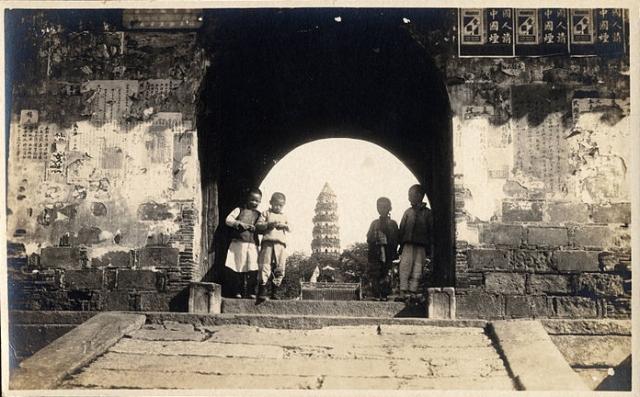 Four Chinese boys standing in a gateway, Kuling, Jiangxi, China, ca.1900-1932 (Wikipedia Commons)